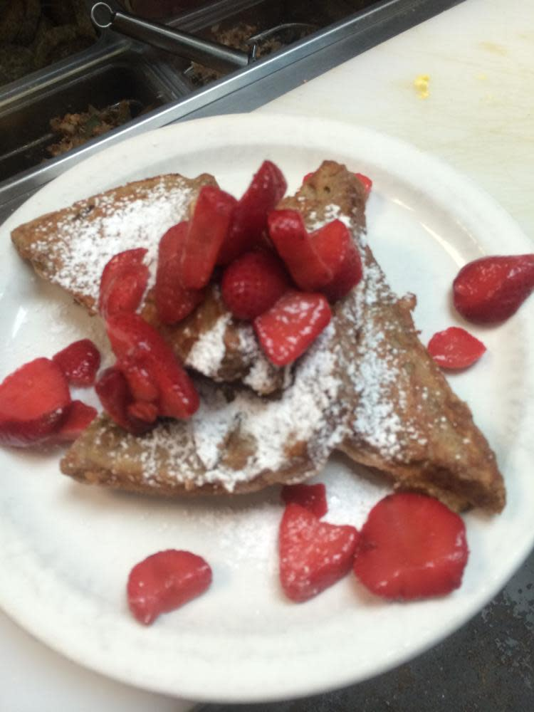 Strawberry Cheesecake French Toast - Sour dough bread with sweetened cream cheese filling marinated in eggs, cinnamon, and vanilla topped with fresh strawberries and dusted with powdered sugar at The Sunflower Cafe