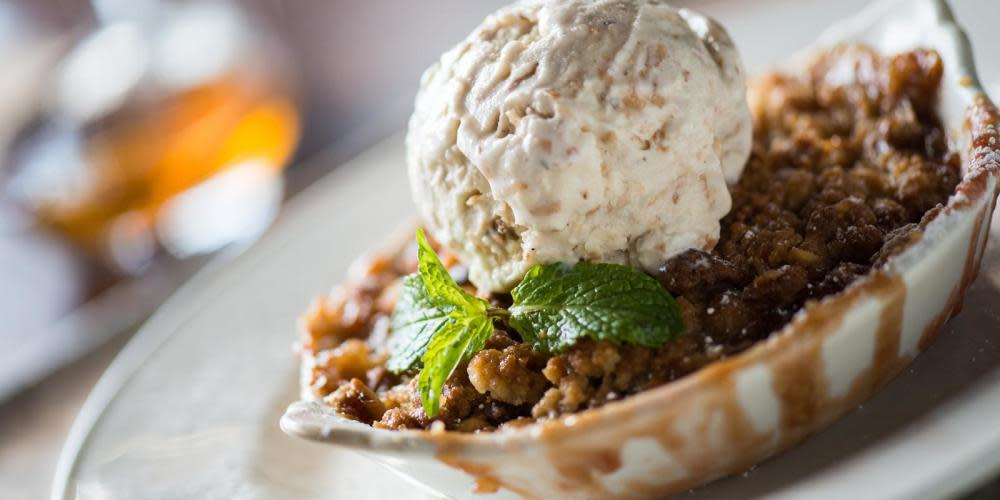 Delight in a spoonful of the Banana Berry Rum Macadamia Nut Crumble topped with toasted coconut ice cream.