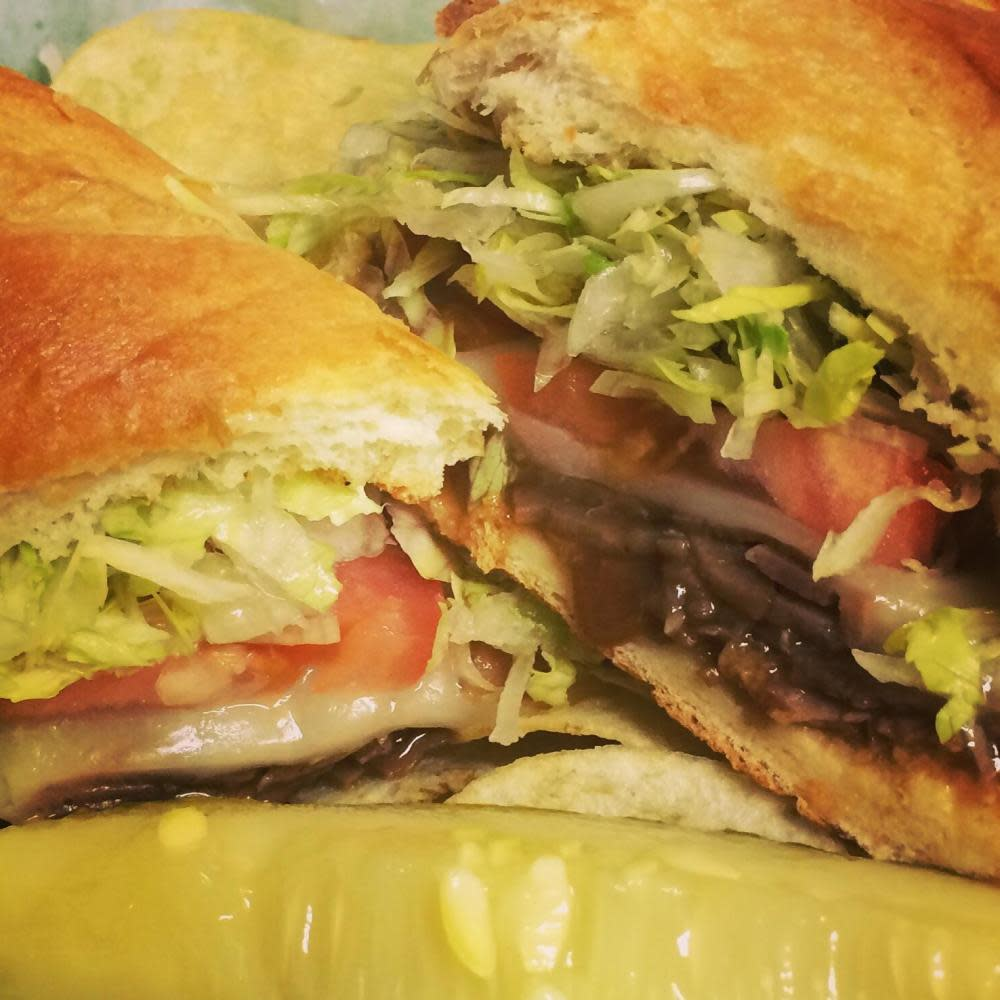 Roast beef covered with brown gravy and provolone cheese and topped with lettuce and tomatoes