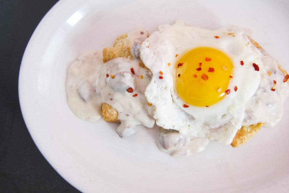 house-smoked brisket gravy on our buttermilk biscuit topped with two sunny side up eggs at Southport Grocery and Cafe