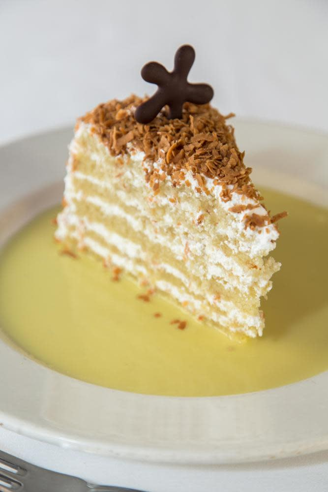 A coconut chiffon cake layered with an Italian buttercream, toasted coconut, and topped with a vanilla crème anglaise at Dickie Brennan's Steakhouse