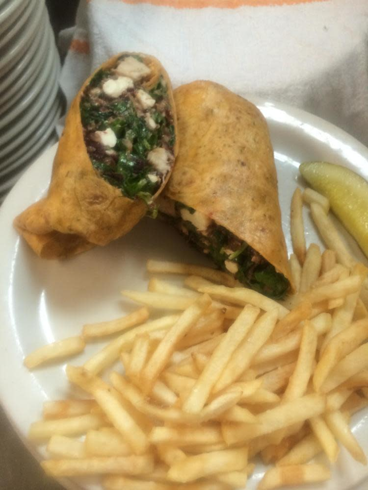 Bog - Grilled chicken breast, wilted spinach, sun dried cranberries, toasted pecans, and feta cheese wrapped in a sun dried tomato tortilla at The Sunflower Cafe